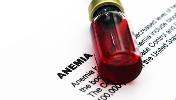 "A container with blood in it lying on top of a piece of paper saying ""anemia""."