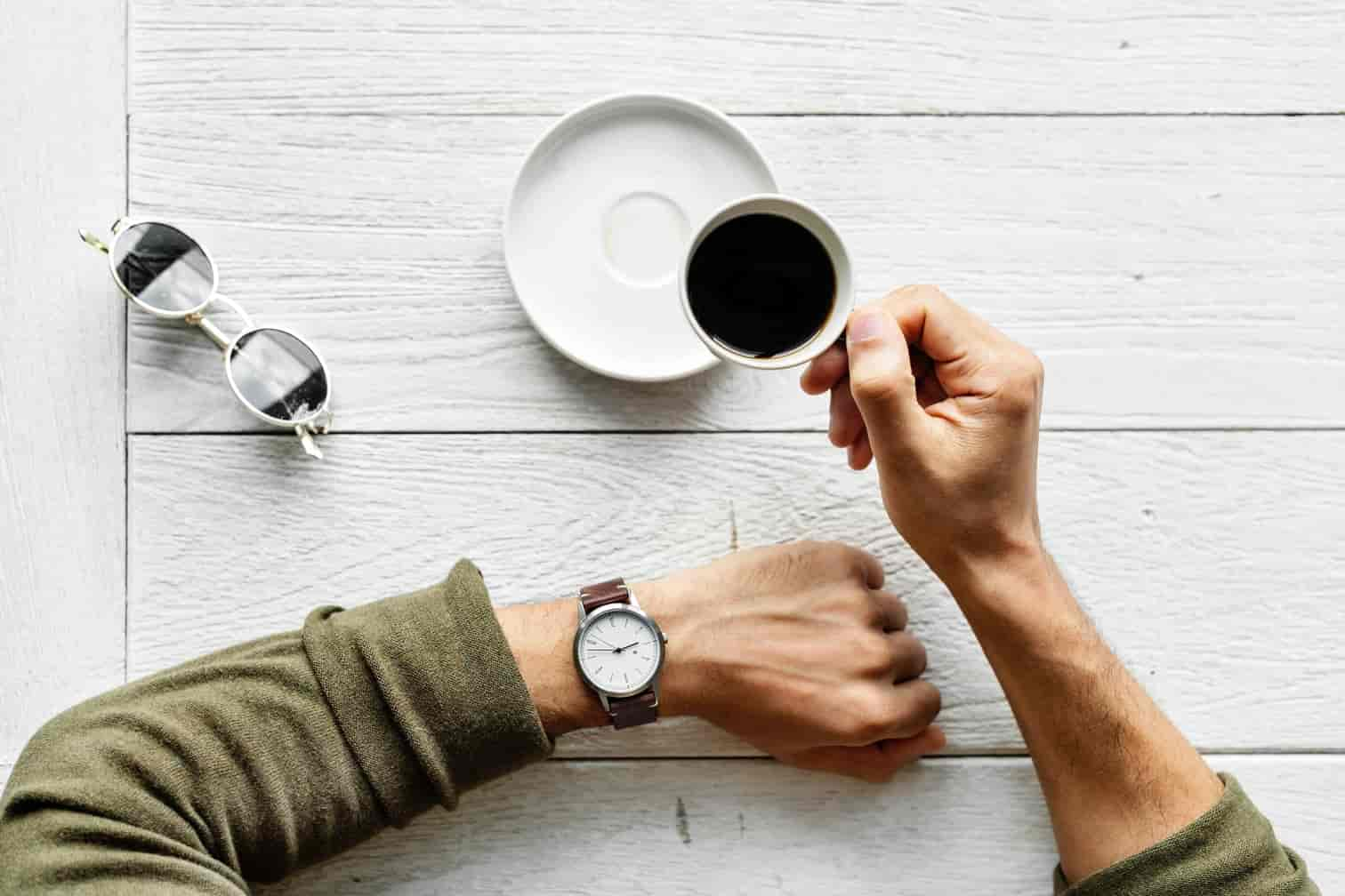 Man holding a cup of coffee and looking at his watch.