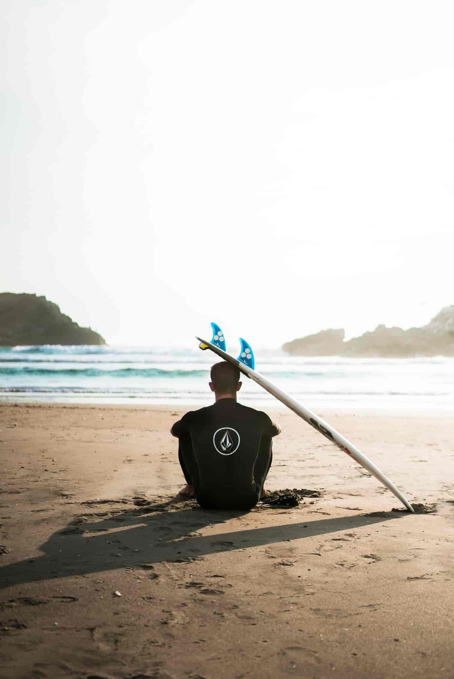 Man sitting on the beach with a surfboard leaning on his head.
