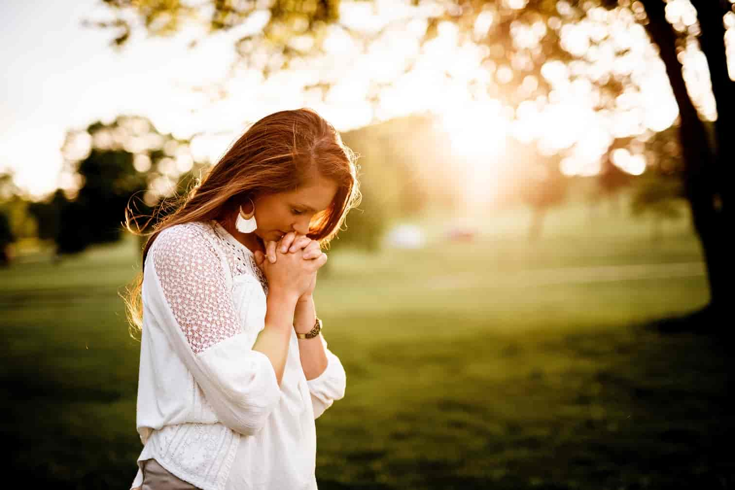Woman standing up and praying.