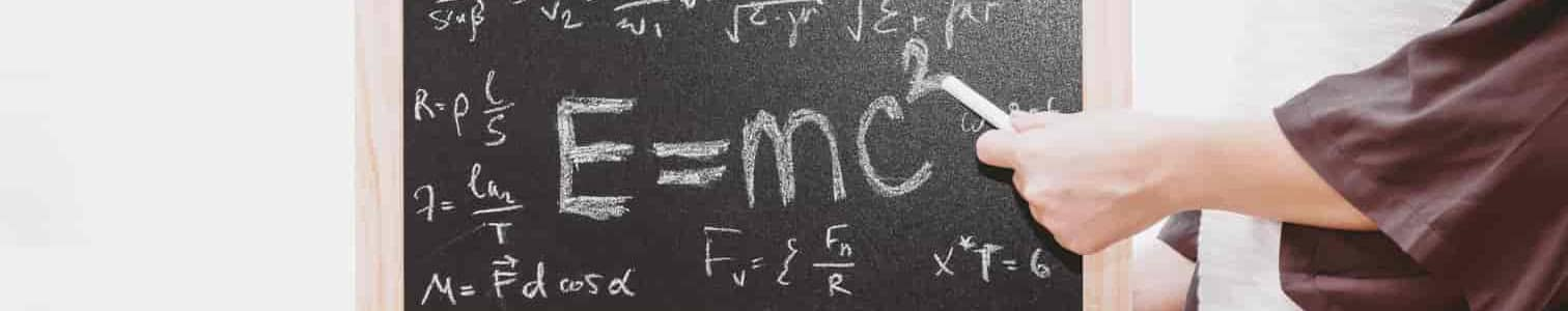"A woman with a chalk board pointing to the word "" E=mc2""."